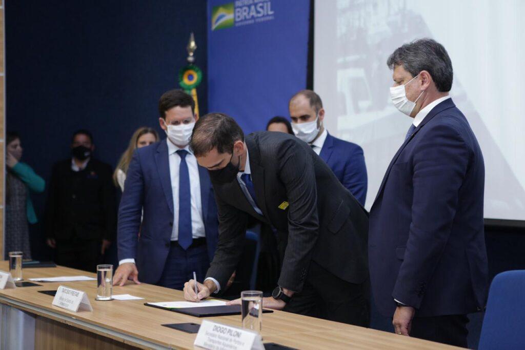 Presidente do Enseada, Mauricio de Almeida, assina documento ao lado do Ministro Tarcísio de Freitas